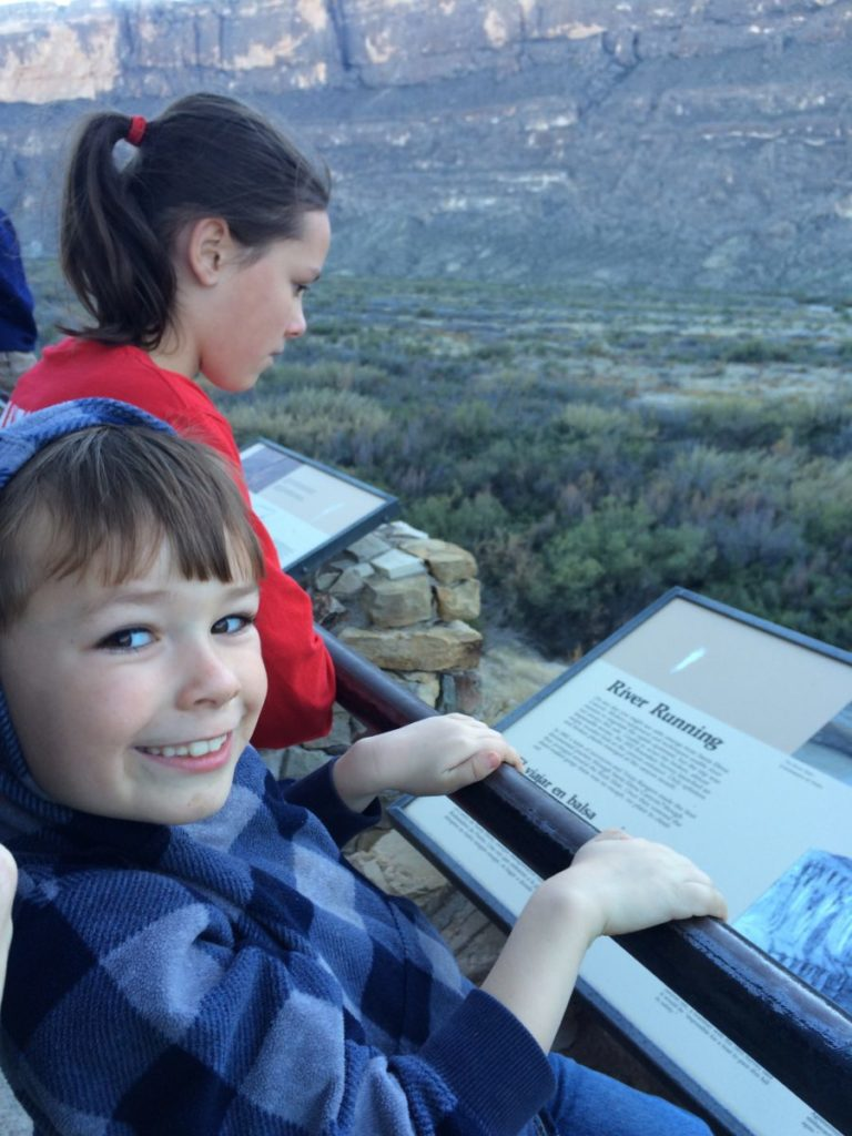 The carful of kids take in a moment to read about the canyon.