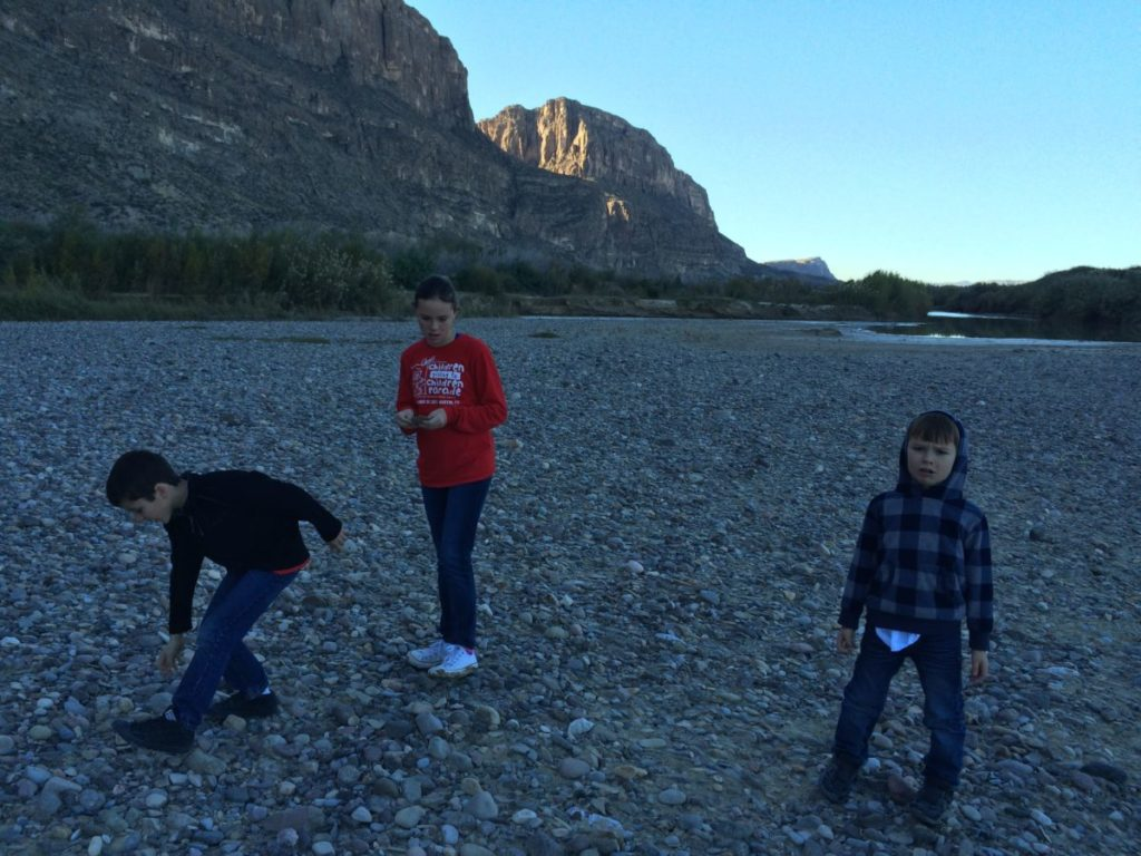 The carful of kids look for the perfect rock to skip along the Rio Grande in Santa Elena Canyon. Big Bend National Park for kids,