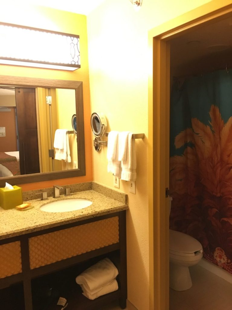 The bathroom of the Caribbean Beach Resort has a double sink vanity and lighted make-up mirror. Walt Disney World,